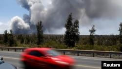 ລົດຄັນນຶ່ງກຳລັງແລ່ນຜ່ານຂີ້ຝຸ່ນ ທີ່ພຸ້ງຂຶ້ນຈາກຂຸມຮາເລີໂມໂມ ຢູ່ຈອມພູໄຟ ຄີໂລເວອາ (Kilauea) ວັນທີ 25 ພຶດສະພາ 2018.