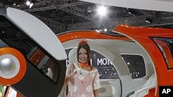 "A model sits on Suzuki Motor Corp.,'s concept car ""Q-Concept"" during the press preview of Tokyo Motor Show in Tokyo."