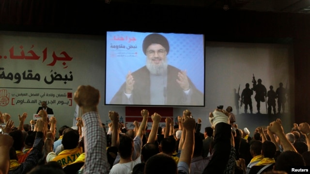 Lebanon's Hezbollah leader Sayyed Hassan Nasrallah addresses his supporters from a screen during a rally to commemorate Hezbollah Wounded Veterans Day in Beirut suburbs, Lebanon, June 14, 2013.