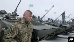 ນາຍທະຫານຢູເຄຣນ ຄົນໜຶ່ງຢືນຢູ່ໃກ້ໆກັບ ລົດຖັງທັງຫຼາຍ ໃນລະຫວ່າງ ພິທີສົ່ງມອບອຸປະກອນ ທາງດ້ານທະຫານ ຫຼາຍກວ່າ 100 ຊະນິດ ແກ່ກອງທັບຢູເຄຣນ ໂດຍມີປະທານາທິບໍດີ Petro Poroshenko ເຂົ້າຮ່ວມ ເພື່ອເປັນຂີດໝາຍການສົ່ງມອບນີ້ ຢູ່ໃກ້ໆກັບ ເມືອງ Zhitomir ຂອງຢູເຄຣນ, ວັນທີ 5 ມັງກອນ 2015.
