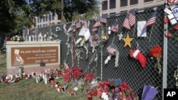 FILE - Flowers and American flags honoring the 14 victims of the Dec. 2, 2015, terror attack in San Bernardino, California, Dec. 29, 2015. Apple refused to help the FBI unlock an iPhone belonging to one of the assailants.