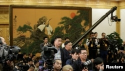 FILE - Journalists wait for a meeting before China's President Xi Jinping and other new Politburo Standing Committee members arrive at the Great Hall of the People in Beijing, Oct. 25, 2017.