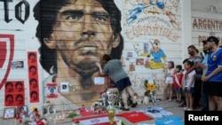 Warga Argentina berduka cita atas meninggalnya legenda sepakbola Diego Armando Maradona, di luar stadion Diego Armando Maradona di Buenos Aires, Argentina Rabu (25/11).