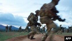 Des soldats traversent une route lors d'un exercice militaire de l'unité d'entraînement de l'armée britannique au Kenya (BATUK) avec les Forces de défense du Kenya (KDF) au ranch ol-Daiga, sur le plateau de Laikipia au Kenya, le 26 mars 2018.