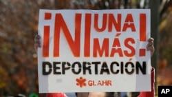 一名男子在美国移民机构所在的办公楼前举行的抗议期间高举要求停止遣返非法移民的标语。(资料照)