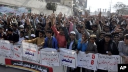 Pakistani protesters condemn the suicide bombing at the Lal Shahbaz Qalandar shrine, in Lahore, Pakistan, Feb. 17, 2017. Pakistani forces killed and arrested dozens a day after a massive suicide bombing by the Islamic State group killed dozens of worshipp