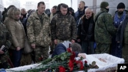 FILE - Fellow Ukrainian government soldiers and mourners bid farewell to Oleksandr Ilnitsky, who was shot dead by a pro-Russian rebel sniper in Ukraine's eastern Donetsk region, during a service in Kyiv's Independence Square, Jan. 11, 2016.