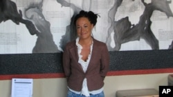 File - Rachel Dolezal, president of the Spokane, Washington, chapter of the NAACP, stands in front of a mural she painted, in Coeur d'Alene, Idaho.