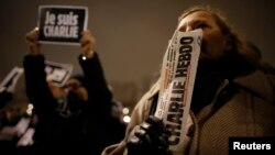 A man holds a copy of weekly satirical magazine Charlie Hebdo to pay tribute during a gathering at the Place de la Republique in Paris Jan. 7, 2015. Seorang pria memegang sebuah eksemplar tabloid Charlie Hebdo
