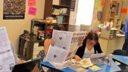 Little Wound journalism class students check their published work.