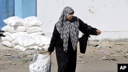 A Palestinian woman drags a sack of flour received as food supplies at a United Nations food aid distribution center, Shati refugee camp, Gaza City. (file)