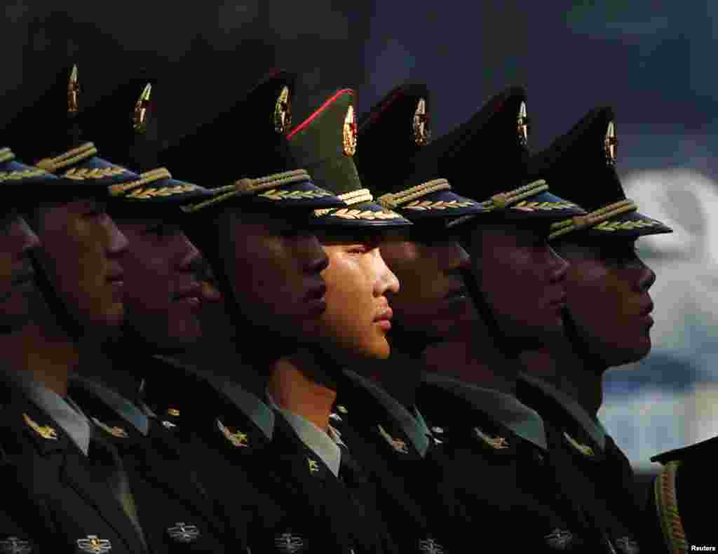 Members of an honor guard stand in line as they prepare for a welcoming ceremony for visiting Vietnamese President Truong Tan Sang outside the Great Hall of the People in Beijing, China.