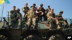 3일 우크라아나 서부 리비우에서 미국-우크라이나 연합 군사훈련이 실시된 가운데, 아르세니 야체뉵 우크라이나 총리(가운데)가 군인들과 탱크 위에 앉아서 훈련을 지켜보고 있다.