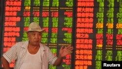 23일 중국 안후이성 푸양의 증권거래소에서 투자가가 전광판에 나타난 주가지수에 반응하고 있다.