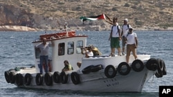 "Supporters of a Gaza-bound flotilla wave a Palestinian flag as one of the flotilla's boats ""Juliano"" departs from Perama port near Athens for a town on the southern Greek coast, July 6, 2011"
