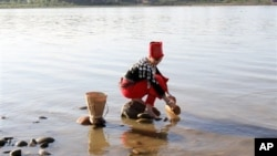 In this photo taken on Jan. 7, 2011, clad in traditional dress a woman from Kachin race uses a bamboo container to fetch water from the Irrawaddy River in Kachin State, northern Myanmar. The country's President Thein Sein called Friday, Sept. 30, 2011 for