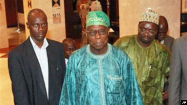 Former Nigerian President Olusegun Obasanjo, center, leaves his hotel for a meeting with incumbent Ivorian President Laurent Gbagbo in Abidjan, Ivory Coast.