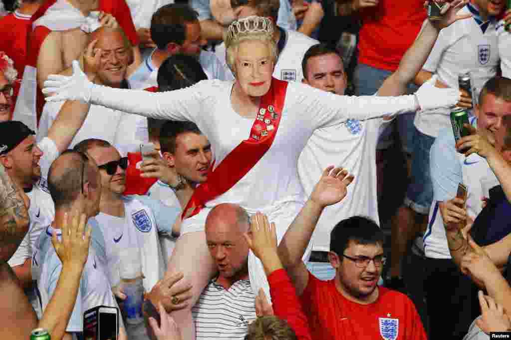 An English fan wears a mask of Queen Elizabeth II in Saint Etienne, France, before the Euro 2016 football match between England and Slovakia.