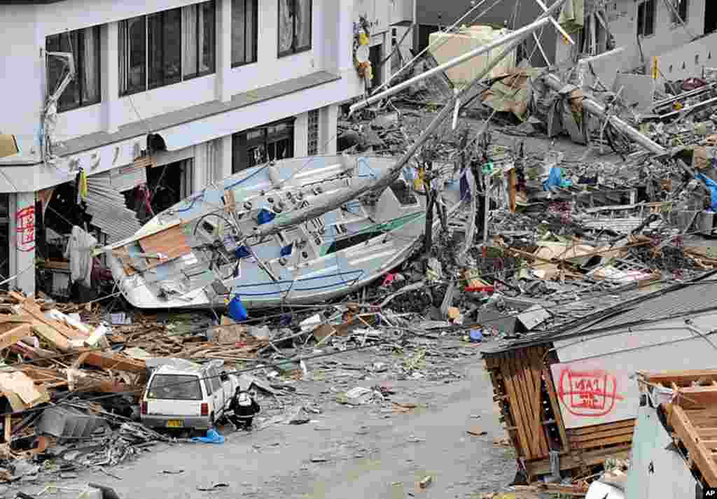 A yacht lies beside a building in the devastated city of Ofunato, Iwate prefecture as the country struggles to cope following the earthquake and tsunami disasters, March 15, 2011. (AFP)
