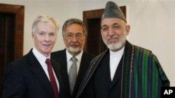 阿富汗總統卡爾扎伊(右)和美國駐阿富汗大使克羅克(左)於去年7月25日會面時握手。(資料圖片)