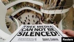 """عکس آرشیوی از پوستری در دست یک خبرنگار روزنامه """"زمان"""" در اعتراض به حملات پلیس ترکیه به دفاتر رسانه های آن کشور - آذر ماه ۱۳۹۳"""