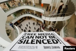 FILE – A journalist holds a banner at the headquarters of Zaman daily newspaper in Istanbul on Dec. 14, 2014, after Turkish police raided a television station and newspaper.
