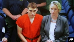 A video monitor shows school shooting suspect Nikolas Cruz, left, making an appearance before Judge Kim Theresa Mollica in Broward County Court, Feb. 15, 2018, in Fort Lauderdale, Florida. Cruz is accused of opening fire Wednesday at the school killing more than a dozen people and injuring several.