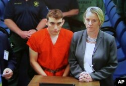 FILE - A video monitor shows school shooting suspect Nikolas Cruz, left, making an appearance before Judge Kim Theresa Mollica in Broward County Court, Feb. 15, 2018, in Fort Lauderdale, Florida.