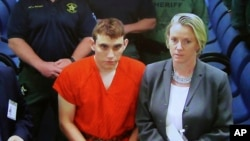 FILE - A video monitor shows school shooting suspect Nikolas Cruz, left, making an appearance before Judge Kim Theresa Mollica in Broward County Court, Thursday, Feb. 15, 2018, in Fort Lauderdale, Florida.