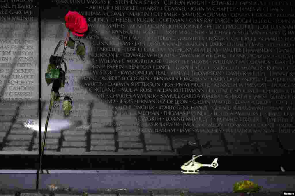 A rose and a toy helicopter are seen next to the Vietnam Veterans Memorial wall during Veterans day in Washington, D.C.