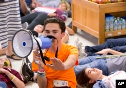 Marjorie Stoneman Douglas High School student David Hogg speaks as demonstrators lie on the floor at a Publix Supermarket in Coral Springs, Fla., May 25, 2018.