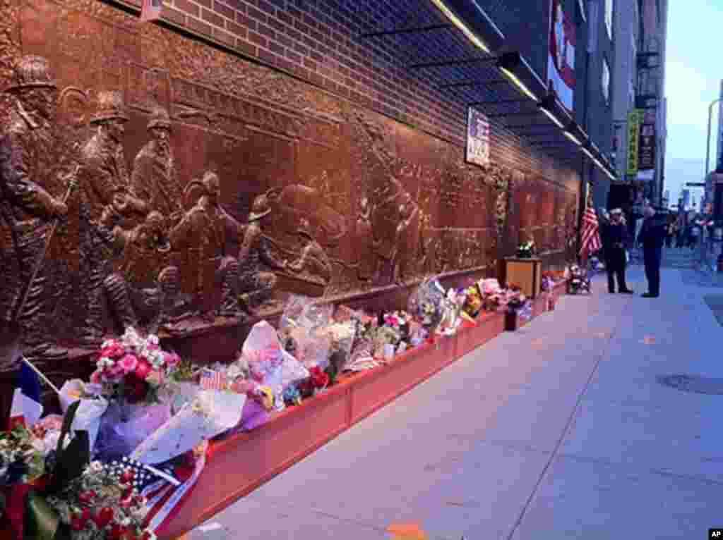 Flowers left along the bronze firefighter memorial outside the World Trade Center memorial, September 11, 2011 (VOA - C. Presutti)