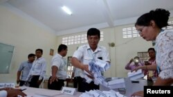 FILE - Members of the National Election Committee count ballots during a Senate election in Phnom Penh, Cambodia, Feb. 25, 2018. The committee was one of several organizations apparently caught up in a recent cyberattack engineered by the Chinese government, investigators allege.