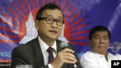 Cambodian opposition leader Sam Rainsy, left, who is currently living in exile in France, talks about the opposition's plans for 2013 elections in Cambodia during the launching of the International Parliamentary Committee for Democratic Elections in Cambodia with Philippine Sen. Franklin Drilon Monday, Sept. 10, 2012, in San Juan, east of Manila, Philippines.