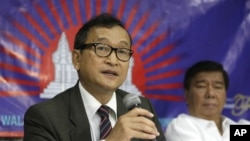 Cambodian opposition leader Sam Rainsy, left, who is currently living in exile in France.