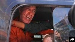 Australian filmmaker James Ricketson speaks from a prisoner van outside Phnom Penh Municipal Court, in Phnom Penh, Cambodia, Aug. 31, 2018.