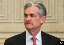 FILE - Federal Reserve Gov. Jerome Powell talks with others before a Board of Governors meeting in Washington, Nov. 30, 2015.