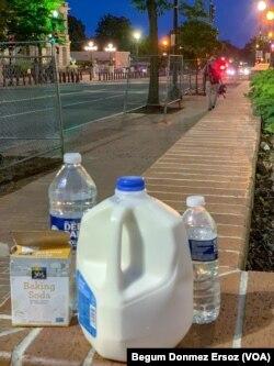 İnsanların göz yaşartıcı gazın etkisini azaltmak için Washington'da sokağa bırakılan süt ve su şişeleriyle karbonat.