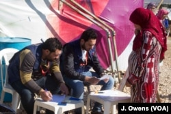 A Syrian women registers her details ahead of collecting items provided to help protect the refugees' makeshift shelters against the elements this winter.
