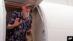 Former hostage Sjaak Rijke, released April 6 by an al-Qaida-related group, waves as he gets off an airplane in Bamako, Mali, April 7, 2015.