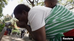 A Zimbabwean woman drinks water from a tap in Harare, May 4, 2010.