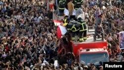 이집트 경찰청 본부 건물에서 발생한 폭탄 테러로 사망한 희생자들의 장례식이 치뤄진 24일 애도객들이 장례차를 쫒고 있다.