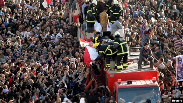 A crowd of mourners surge toward a vehicle carrying wrapped bodies during a funeral service for policemen, people killed in a car bomb explosion, in Egypt's Nile Delta city of Mansoura, about 120 km northeast of Cairo, Dec. 24, 2013.