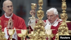 Pope Benedict XVI (R) flanked by Cardinal Tardisio Bertone conducts the holy mass of Pentecost Sunday in Saint Peter's Basilica at the Vatican, May 27, 2012.