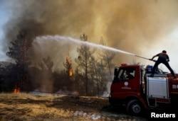 Petugas pemadam kebakaran berusaha memadamkan api di dekat Marmaris, Turki, 1 Agustus 2021. (Foto: REUTERS/Umit Bektas)