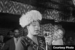 Ella Fitzgerald sings at the Downbeat Club in New York, with Dizzy Gillespie listening, at right in the background, 1947. (William Gottlieb/Library of Congress)