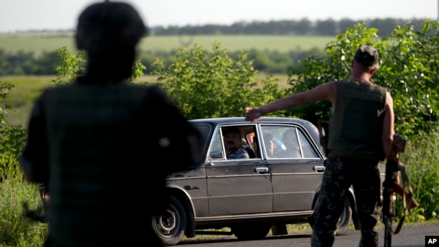 Ukrainian soldiers stop a vehicle at a checkpoint outside the town of Amvrosiivka, eastern Ukraine, close to the Russian border, June 5, 2014.