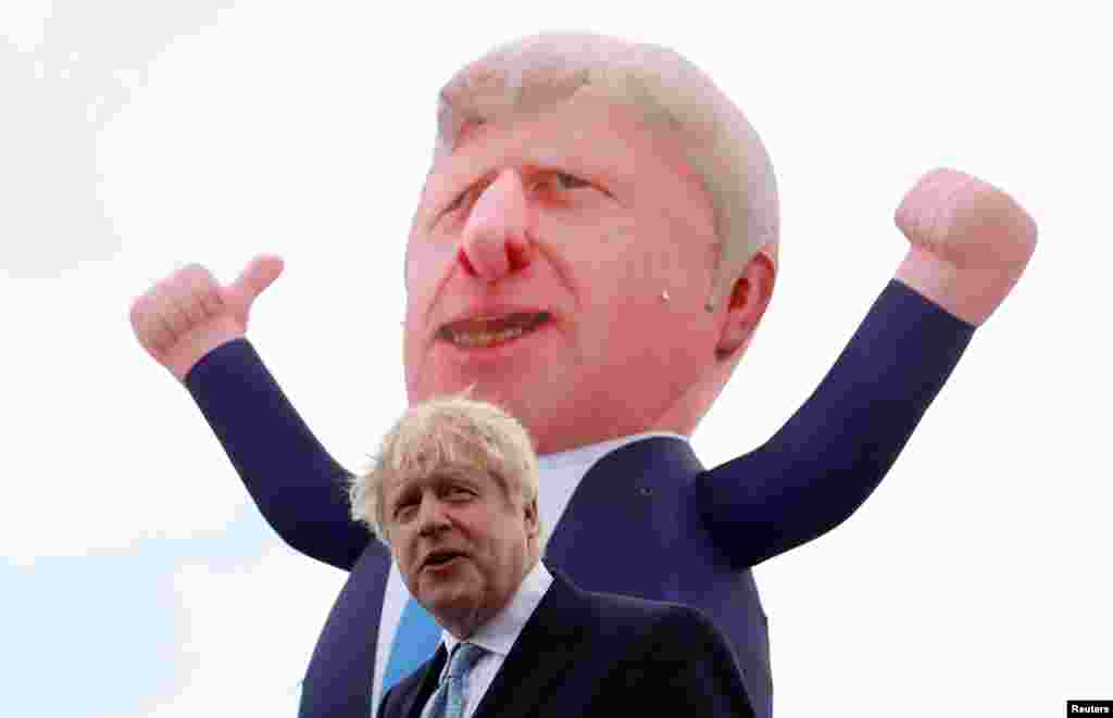 Britain's Prime Minister Boris Johnson speaks, with an inflatable figure depicting him in the background, following local elections at Jacksons Wharf Marina in Hartlepool, Britain.