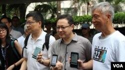 占中三位发起人展示手机电子投票应用程序(美国之音海彦拍摄)