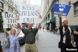 "A man holds a sign reading ""NYC hearts Muslims"" as two other people hold signs reading ""Back the Ban"" and ""Keep Syrians Out"" at protests in response to U.S. President Donald Trump's limited travel ban, approved by the U.S. Supreme Court, in New York City, June 29, 2017."